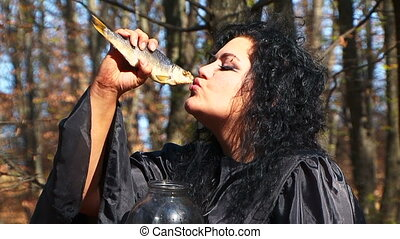 Dark Haired Woman In Black With Dried Fish Posing In Autumn...