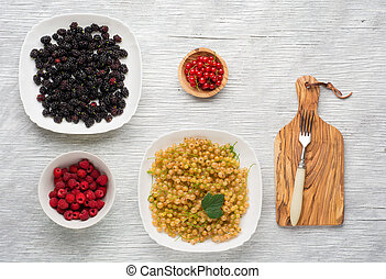 tasty summer fruits on a wooden table. raspberries, mulberry, currant