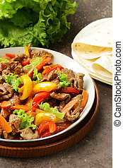 Beef Fajitas with colorful bell peppers in pan on a wooden...