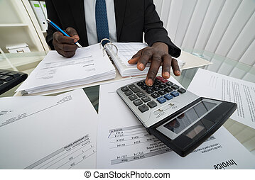 Businessman Calculating Invoices - Close-up Of Businessman...