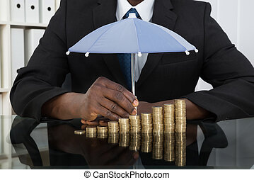 Businessman Protecting Coins With Umbrella - Close-up Of...