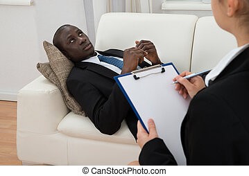 Psychiatrist Making Notes In Front Of Patient