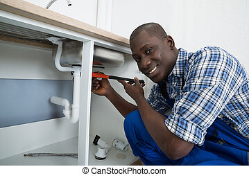 Male Plumber Fixing Pipe Of Sink - Close-up Of Happy African...