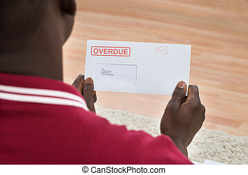 Man Holding Overdue Notice - Close-up Of African Man Holding...
