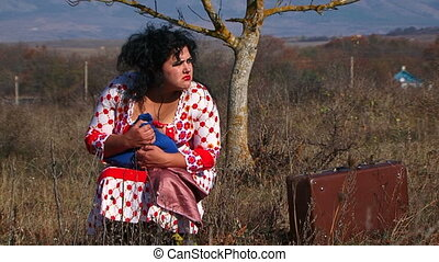 Weird Woman In White Dotted Gown Sitting Near Suitcase At Nature