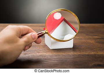 Person Hand With Magnifying Glass And Miniature House -...