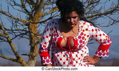 Plus Sized Woman In White Dotted Dress Posing For The Camera At Nature