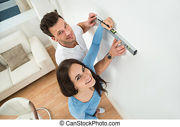 Couple Marking On Wall With Level In New House - Happy...