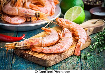 fresh raw prawns on a wooden cutting board with salt,...