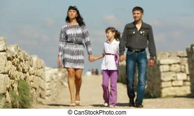 Family Of Three People Walking In The Historical Park.