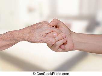 Young woman holding grandma hand - Young woman holding her...