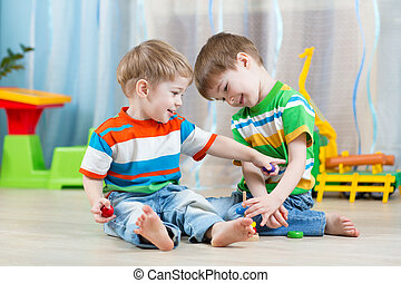 children brothers playing together in nursery  or day care