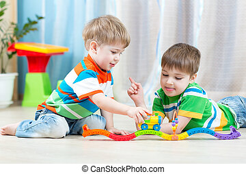 children playing rail road toy in nursery