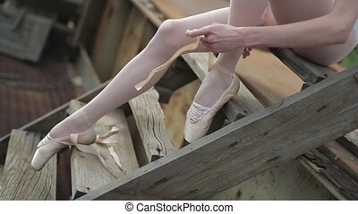 Video footage close-up of a ballet dancer tying ribbons on...