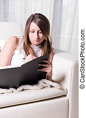 Pretty young girl on couch writing in Book