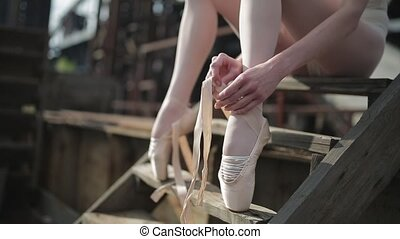 close-up of a ballet dancer tying ribbons on pointe - Video...
