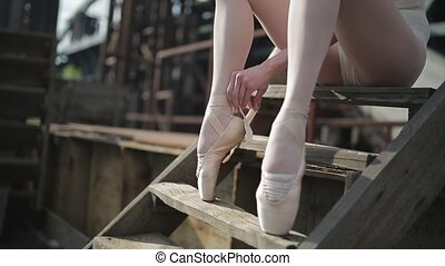 close-up of a ballet dancer tying ribbons on pointe