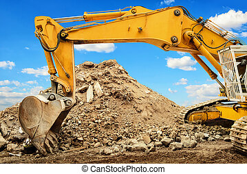 Excavator and heap of dirt in front of blue sky - Yellow...