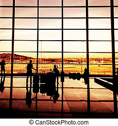Silhouette of airline passengers in an airport lounge at the...