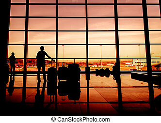 Silhouette of airline passengers in an airport lounge at the wide observation window against a surreal sunset