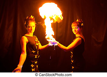 Photo of two women holding fire