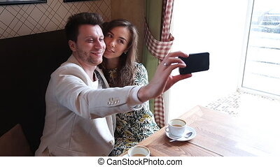 Photo of Couple taking selfie at cafe
