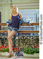 Young sexy woman in blue jeans short in the shop, summer