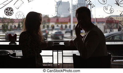 Young fashion elegant stylish couple sitting at a table in a...