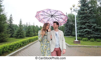 beautiful couple walking under umbrella in forest