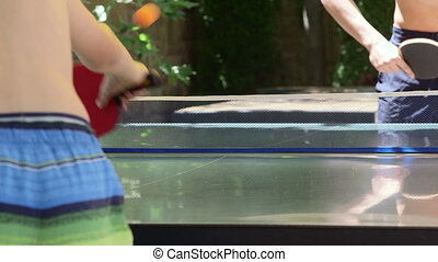 Summer vacation recreation activity boys playing table tennis game outdoor