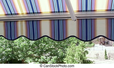 Terrace of hotel with retractable striped awning overlooking seaside