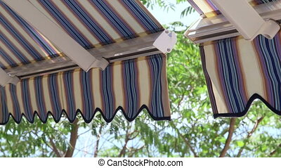 Detail of modern retractable striped awnings over sunny blue...