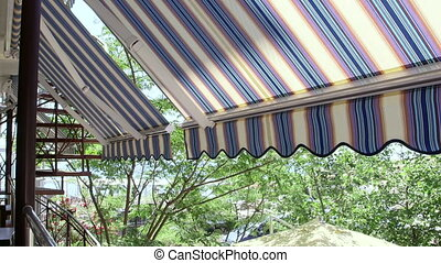 Terrace of hotel with retractable striped awning overlooking...