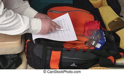 Traveler packing travel bag using checklist of items to pack...