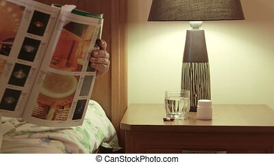 Medication on bedside table woman lying in bed reading magazine