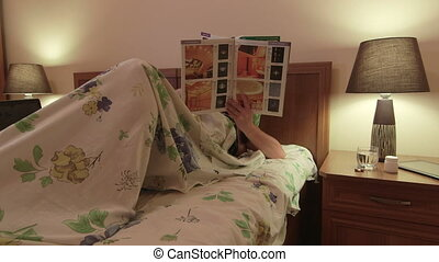Woman lying in bed reading magazine at night