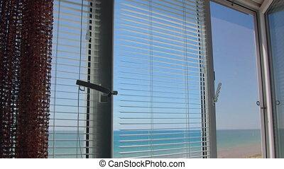 Sea view through the open white window frame