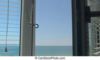 Sea view through the open white window