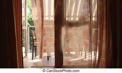 Looking out through open glass door with waving curtain at man drinking coffee