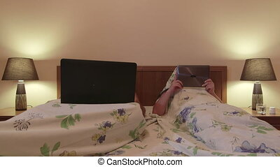 Adult married couple in bed lying side by side using gadgets...