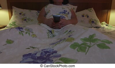 Woman lying on bed with remote control in hand watching TV...