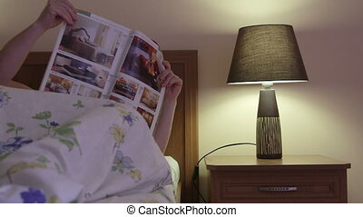 Woman reading a magazine on the bed at night
