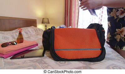 Woman unpacking travel bag with items for beach holiday in hotel room