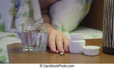 Woman on bed in bedroom taking sleeping pills on bedside table