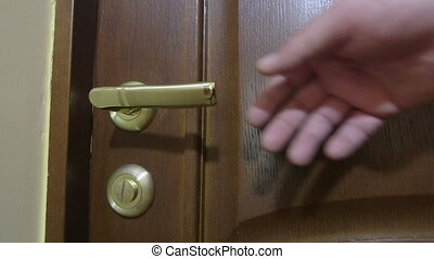 Mans hand opening the door to bedroom with unmade bed