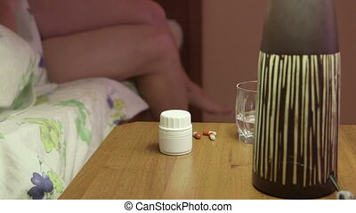 Woman on bed in bedroom taking medication on bedside table