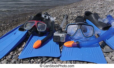 Two snorkeling sets and underwater digital camera on wild...