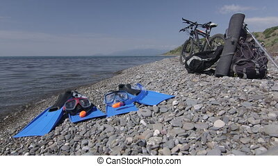 Two bicycles and snorkeling sets on wild pebble beach in...