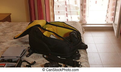 Unpacked professional photo camera backpack on bed in hotel...