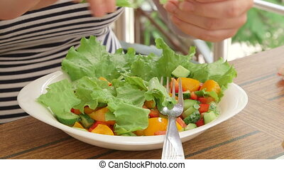 Woman cooking fresh vegetable salad outdoors